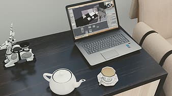 Turned-on laptop computer near teacup
