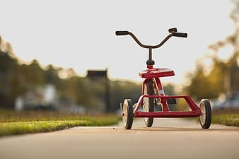 Toddler's red ride-on trike toy under the sunrise