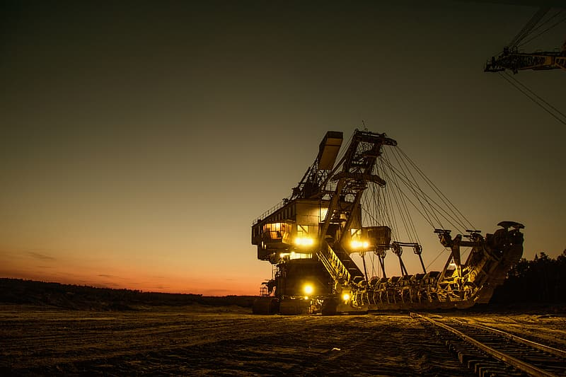 Black and yellow industrial heavy equipment during sunset