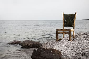 Brown wooden armless chair on seashore