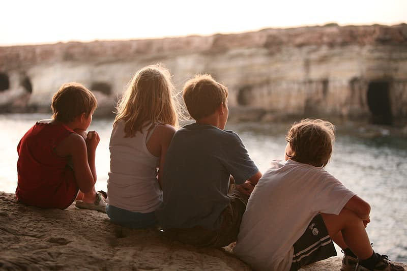 2 boys and 2 girls sitting on brown sand during daytime