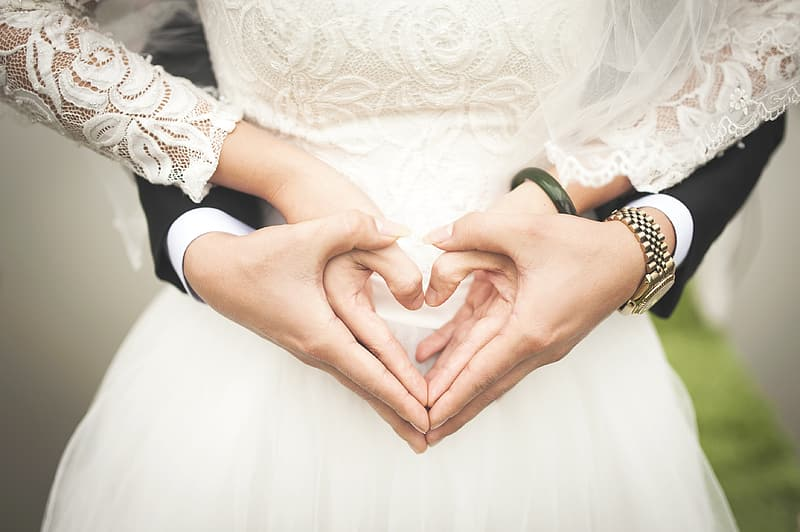 Man and woman holding hands doing heart hand sign