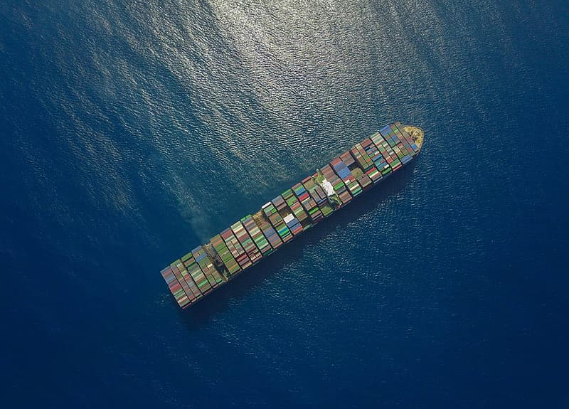 Top view of ship loaded with shipping containers on sea during daytime
