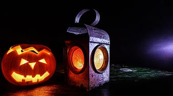 Black metal lantern beside Jack-O-Lantern
