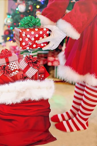 Person wearing Santa costume holding giftbox