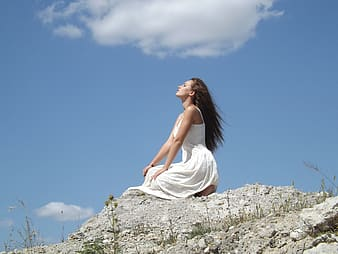Woman in white sleeveless dress looking at sky during daytime
