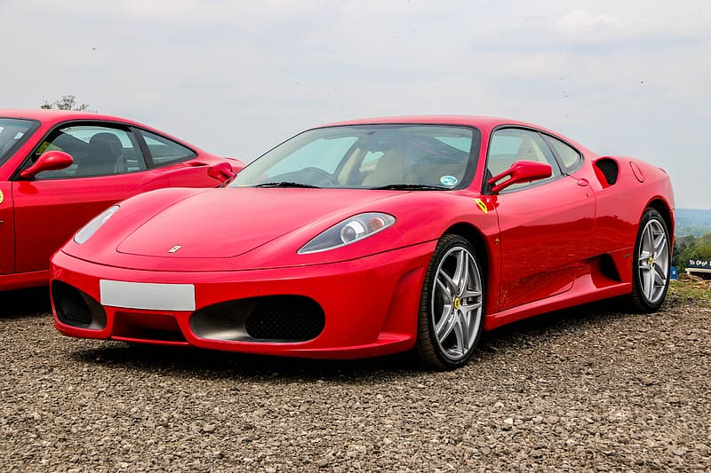 Red Ferrari sports coupe beside red coupe at daytime