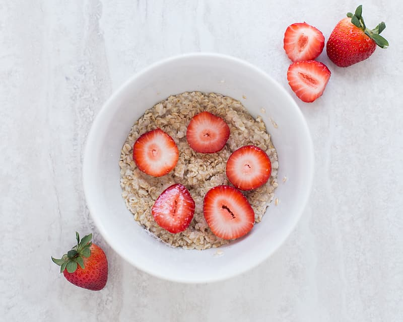 Oatmeal with slice strawberries on bowl