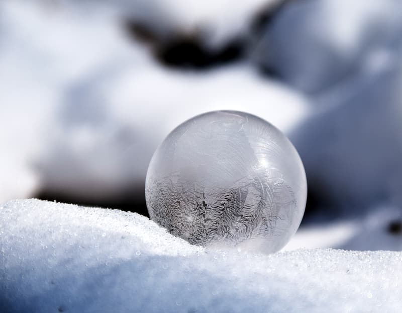 Selective focus of glass ball at snowfield