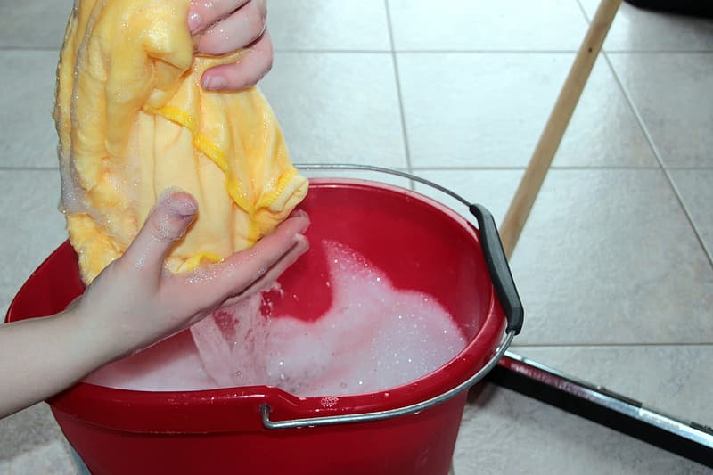 White fabric being washed inside red plastic bucket
