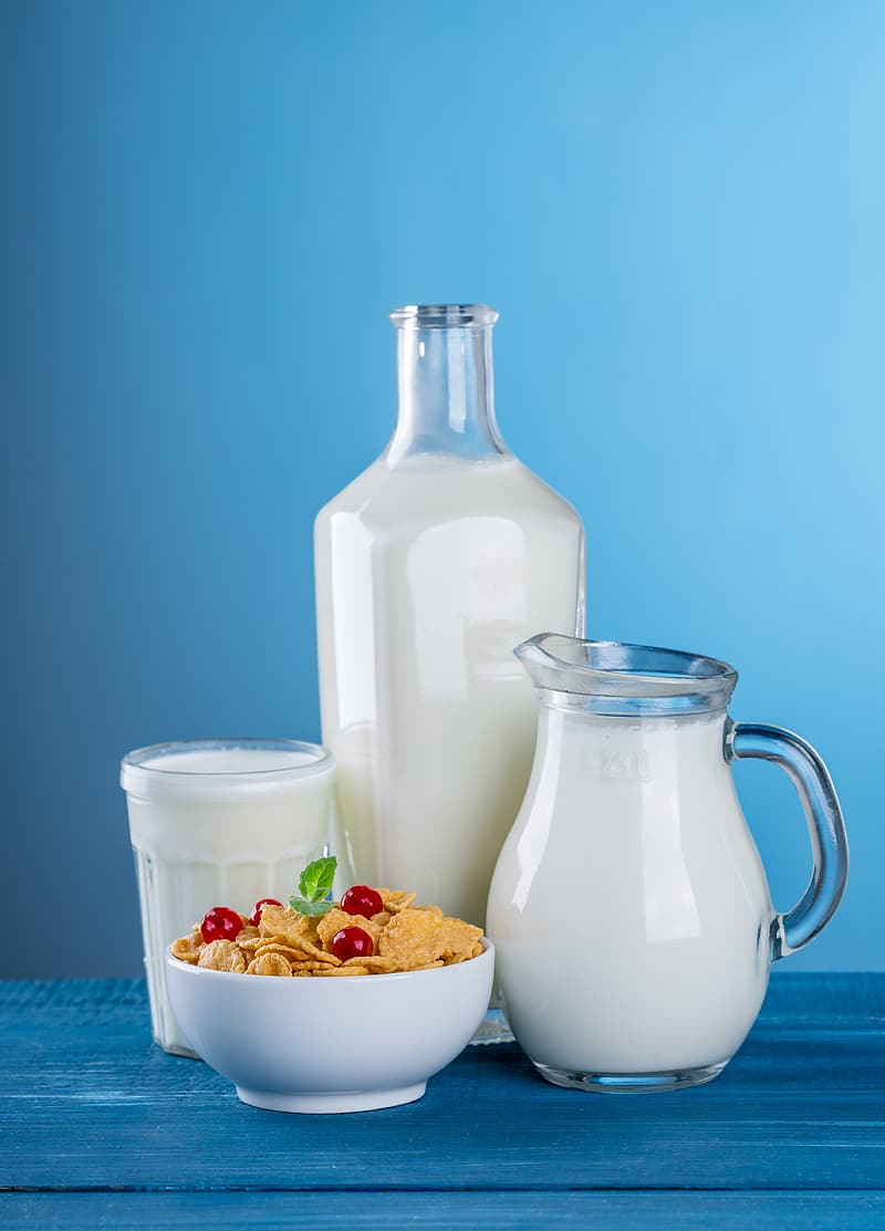 Milk in clear glass pitcher, bottle and drinking glass and cereals on white ceramic bowl