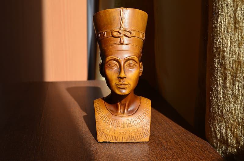 Brown wooden Egyptian headbust on brown wooden table closeup photo