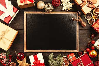 Black and brown wooden board with red and white gift box and silver baubles