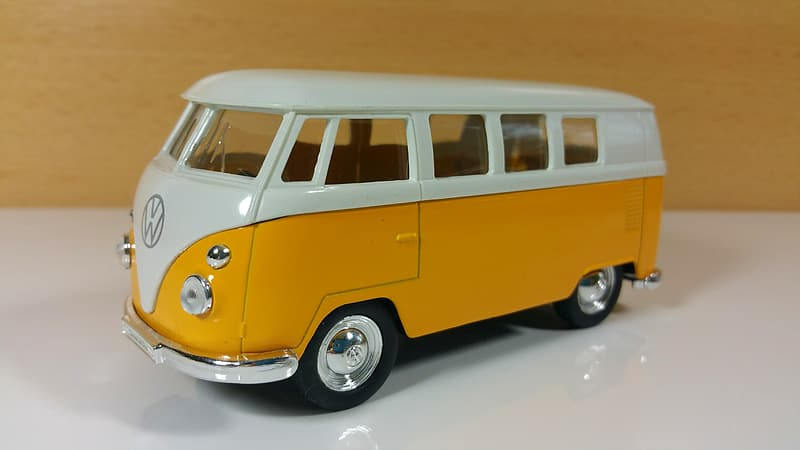 Yellow and white Volkswagen Transporter 2 scale model toy on white surface