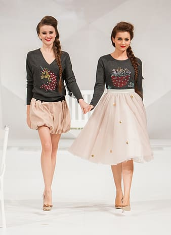Two women holding hands wearing dresses while walking