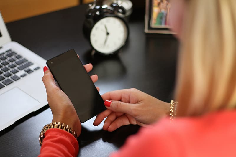 Woman holding black Android smartphone