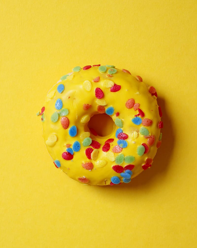 Doughnut with sprinkles on yellow surface
