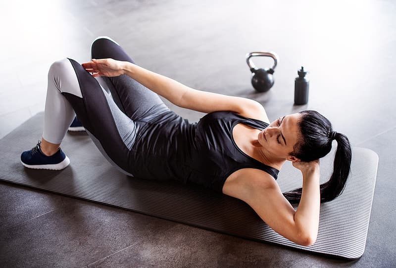 Woman in black tank top and white pants lying on black yoga mat