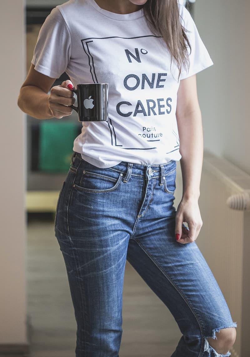 Woman wearing white shirt and blue jeans holding black ceramic coffee mug with Apple logo