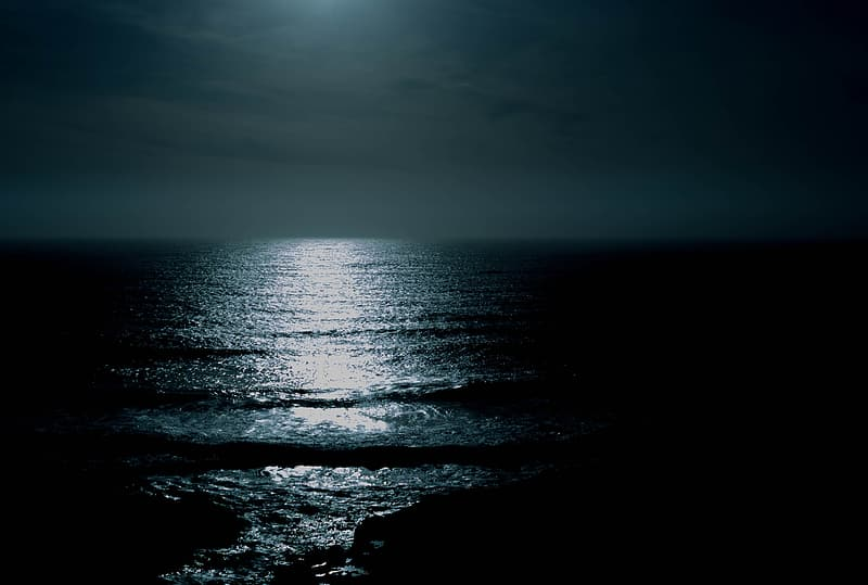 Moon light reflection on body of water during night time
