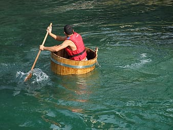 Man on brown wooden boat holding a paddle