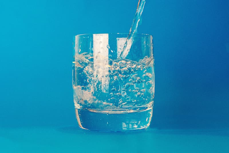 Water pouring on clear glass cup