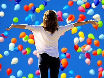 Woman in white blouse under assorted-color balloons