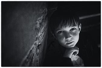 Greyscale photo of boy learning on wall