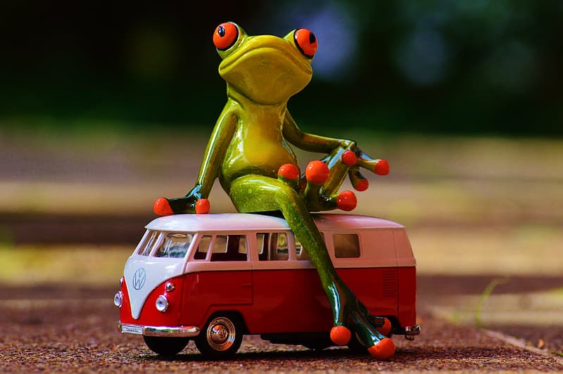 Green frog toy sitting on a red Volkswagen T2 van toy