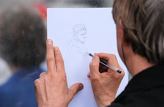 Person sketching a girl on white paper