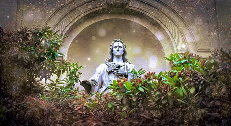 Concrete statue holding cross surrounded by green leaves