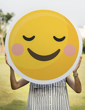 Person holding yellow smiley round plate