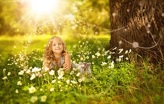 Toddler with gray dress in grass field near tree during daytime