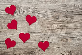 Red heart cardboard cutouts on brown wooden surface