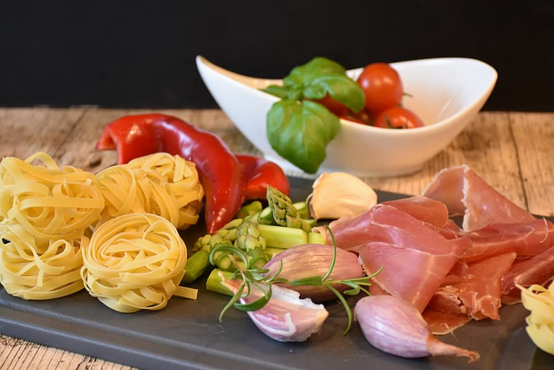 Pasta, bell pepper and raw meat on chopping board