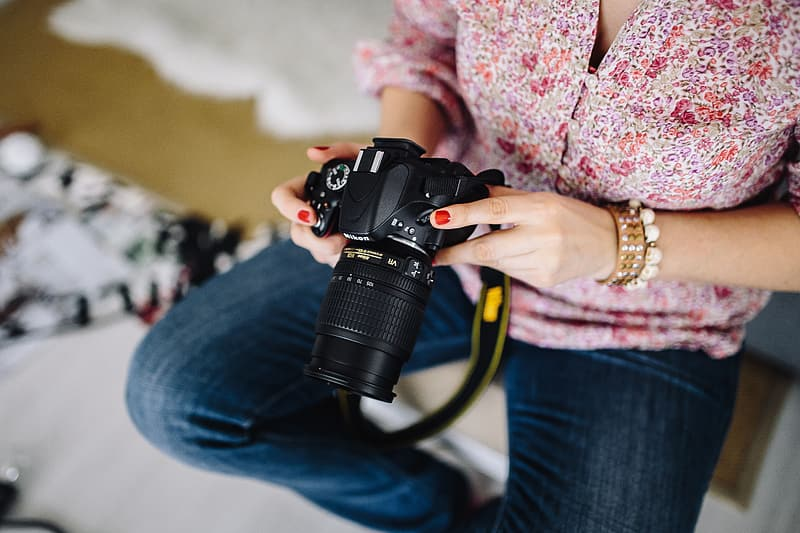 Woman in pink floral long sleeve shirt holding black dslr camera