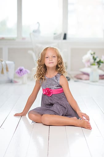 Shallow focus photography of a girl in gray sleeveless dress sitting on white tile flooring during daytime
