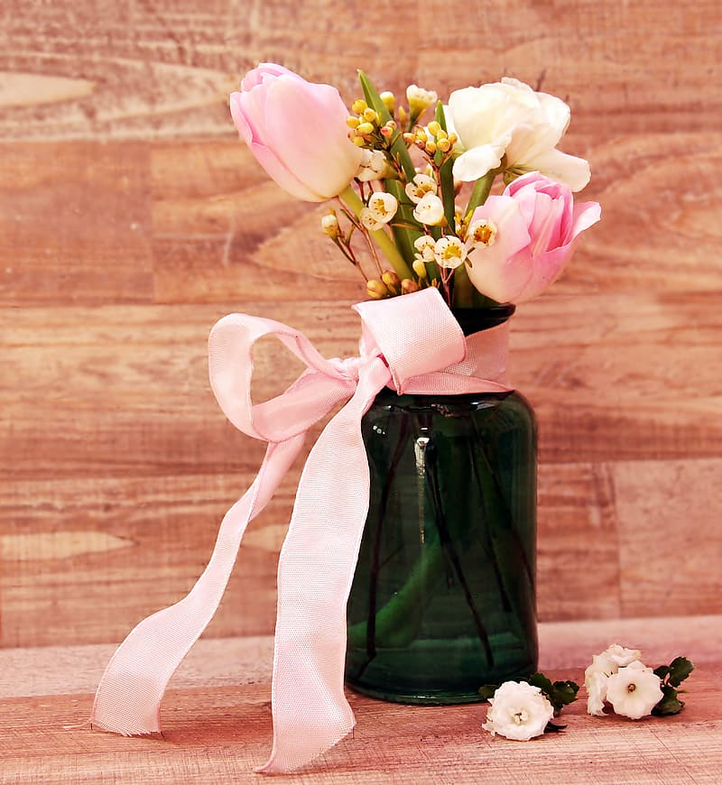 White flowers in green glass vase with pink ribbon