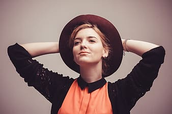Photography of woman in black cardigan and orange shirt wearing hat