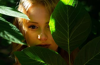 Girl covering her face with green leaves
