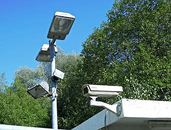 Low angle photography of outdoor post lamp placed near bullet surveillance camera