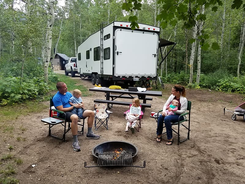 People camping near white RV trailer