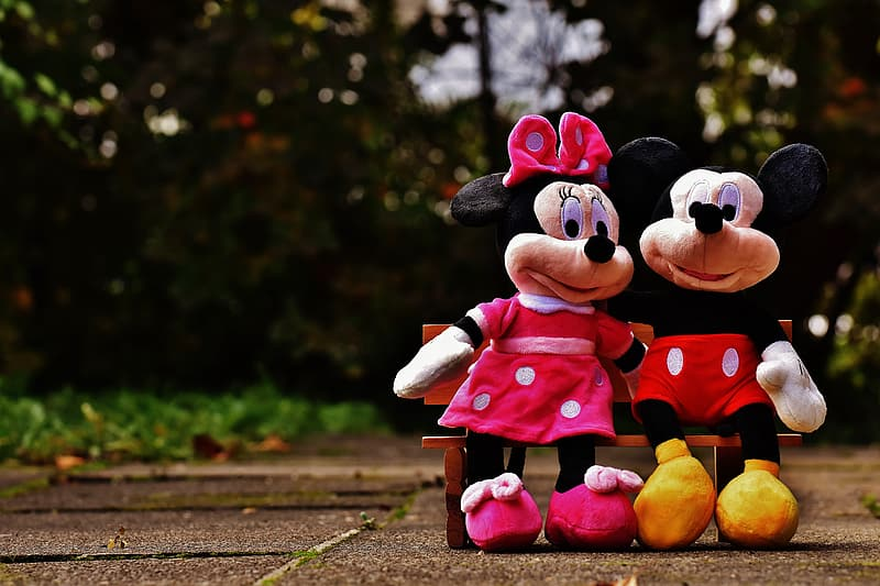 Minnie and Mickey Mouse sitting on bench plush toys