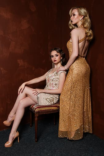 Woman standing beside woman sitting on chair