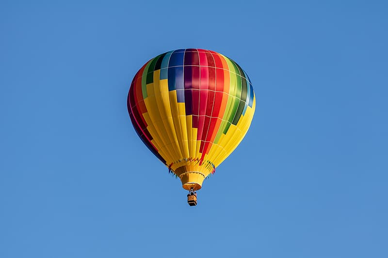 Yellow green and blue hot air balloon in mid air