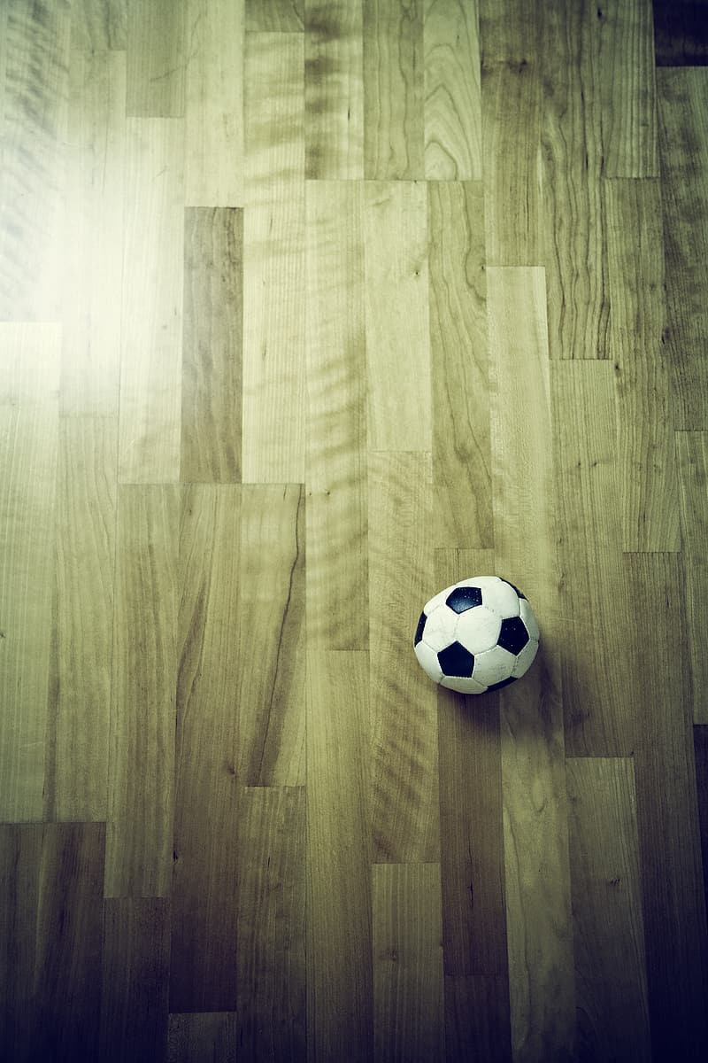 White and black soccer ball on parquet wood flooring