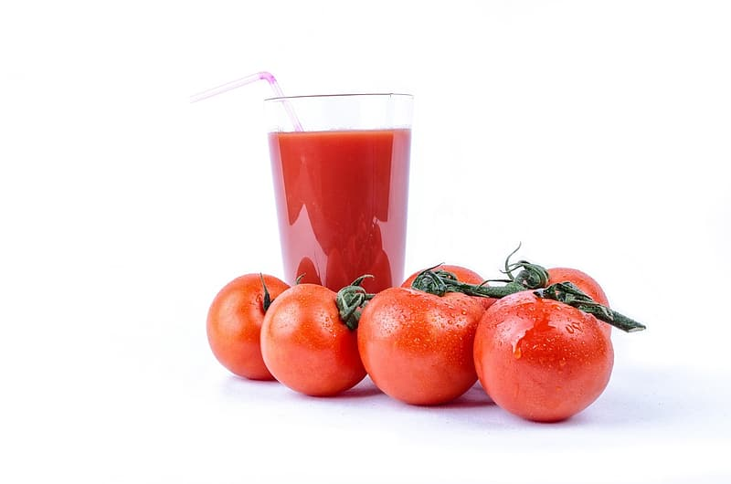 Still life photography of four cherry tomatoes and juice served on clear glass
