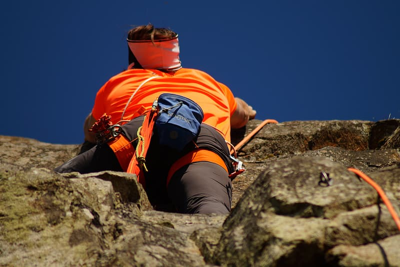 Person climbing on rock under blue sky during daytime