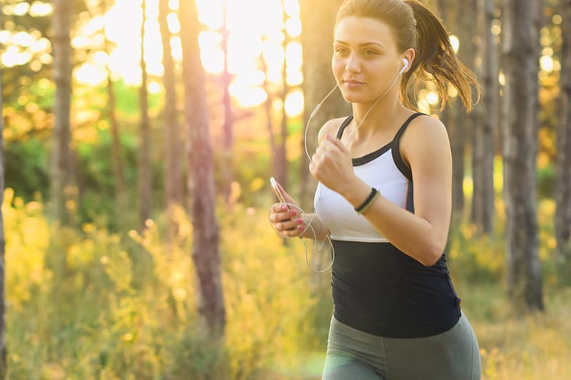 Girl jogging/running exercises workout in the forest using earphones connected to her mobile iPhone smartphone