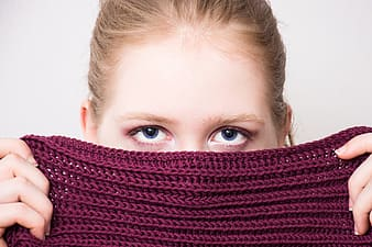 Person covering face with maroon textile
